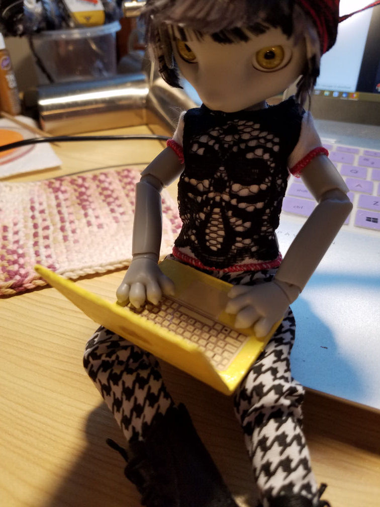A grey Hujoo Phoebe Mouse doll sitting on the edge of a silver laptop with a doll sized pale yellow laptop open on her lap. Looking over the laptop lid we can see the yellow keyboard.