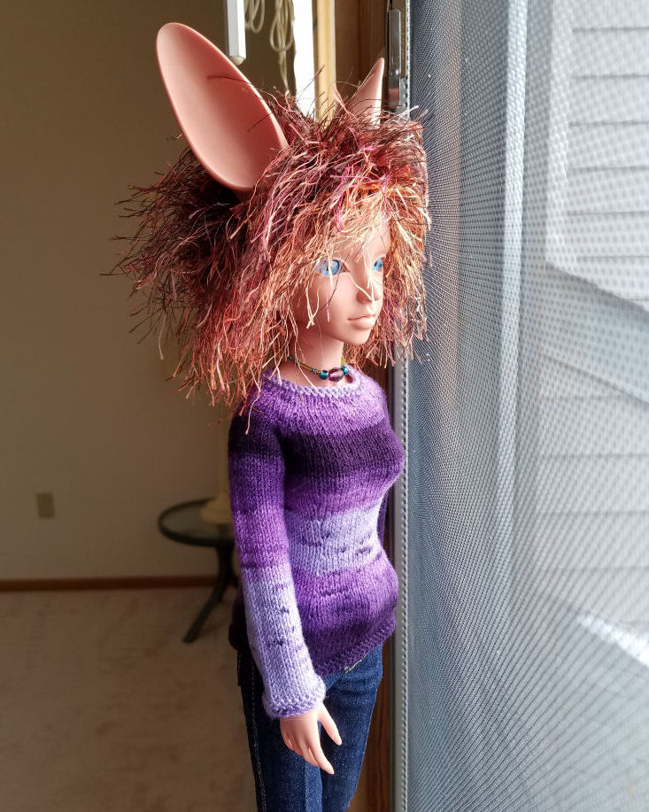 A fennec eared human doll in terracotta colored resin, Featherfall Iruhi, standing looking out the window. She is lit with natural light and is wearing a sweater striped in various shades of purple. The sleeve facing us fades from dark are the shoulder to pale at the cuff.