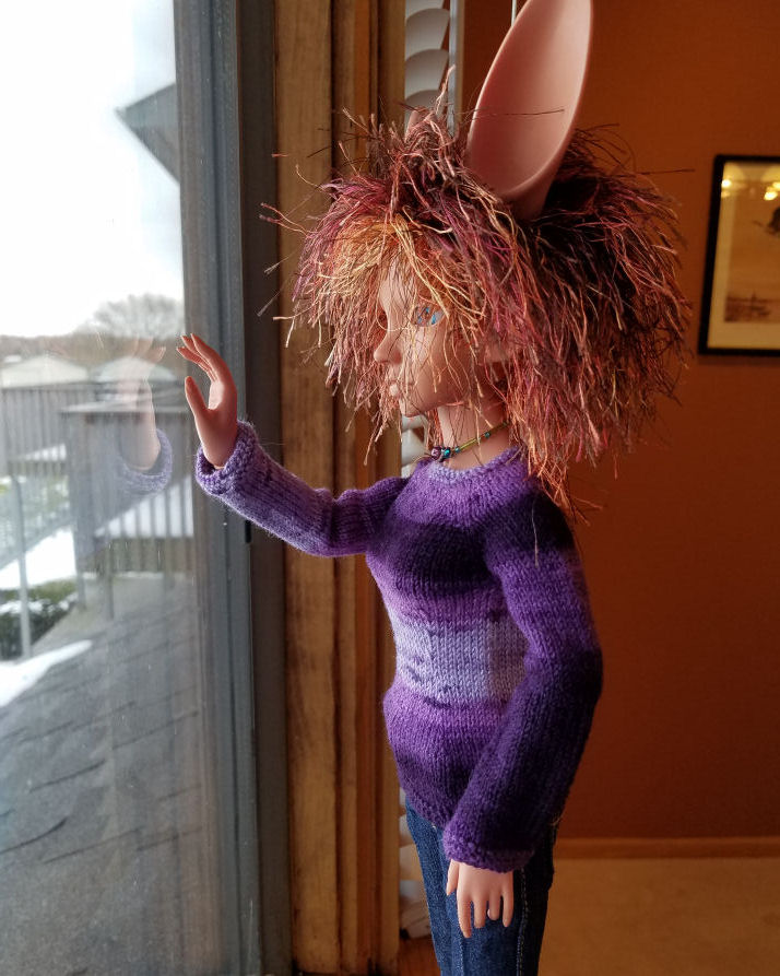 A fennec eared human doll in terracotta colored resin, Featherfall Iruhi, standing looking out the window. She is lit with natural light and is wearing a sweater striped in various shades of purple. The sleeve facing us is mostly dark purple with a band of medium purple around the upper arm from below the shoulder to the elbow.