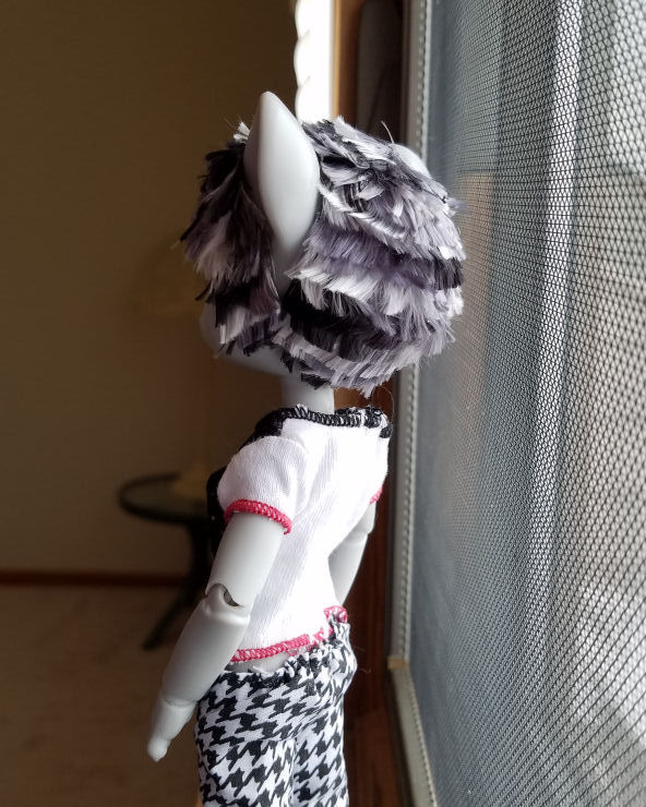 A grey Hujoo Phoebe Mouse doll standing in a window and facing away from the camera. She has a short hairstyle of choppy layers of patchy silver, steel grey, and black hair.