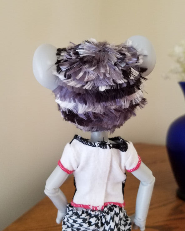A grey Hujoo Phoebe Mouse doll standing facing away from the camera. She has a short hairstyle of choppy layers of patchy silver, steel grey, and black hair. The colors make a horizontal zebra striped sort of pattern.