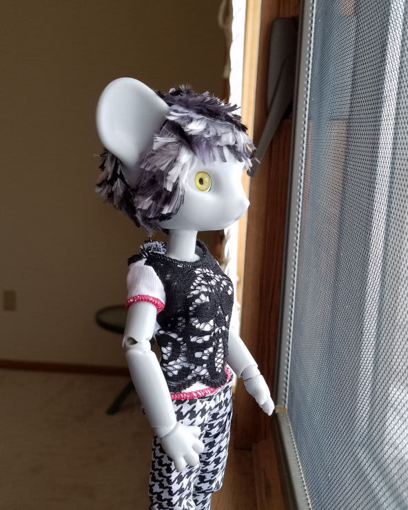 A grey Hujoo Phoebe Mouse doll standing looking out the window. She has a short hairstyle of choppy layers of patchy silver, steel grey, and black hair. we can see how the hair at the back of her head almost meets the hair in front of her ears.
