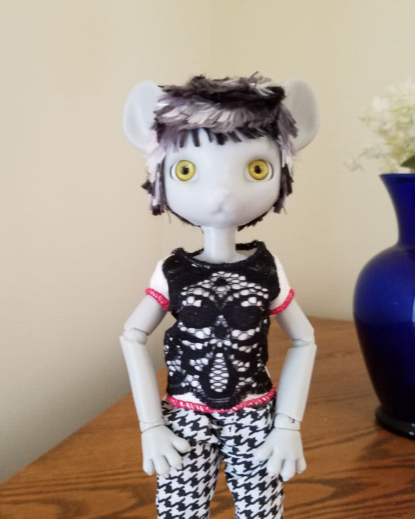 A grey Hujoo Phoebe Mouse doll standing facing the camera. She has a short hairstyle of choppy layers of patchy silver, steel grey, and black hair.