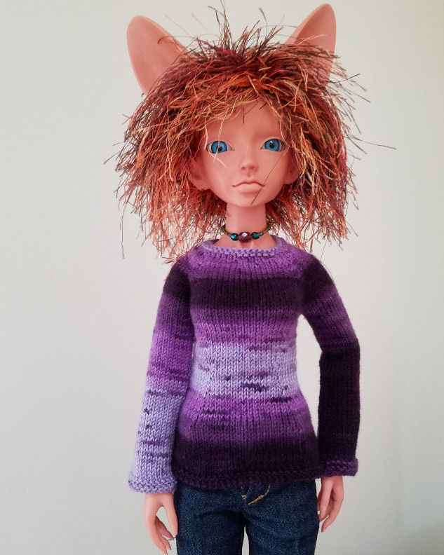 A fennec eared human doll in terracotta colored resin, Featherfall Iruhi, standing looking at the camera. She is wearing a sweater with horizontal stripes of various shades of purple. Her right sleeve fades from dark purple at the shoulder to pale at the cuff. The other sleeve is dark with a band of medium purple around her upper arm. The body of the sweater has a band of dark purple across the bust and hips and fades to pale purple around her neckline and waist.