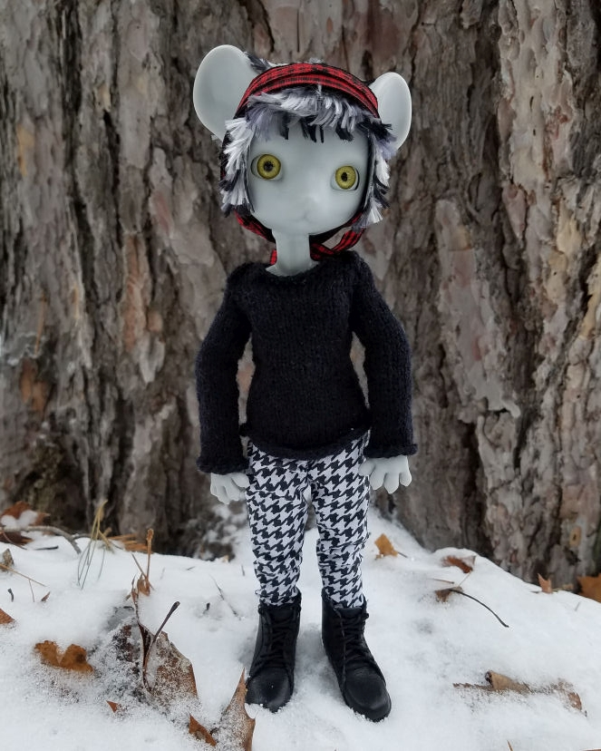 A grey Hujoo Phoebe Mouse doll standing on snow and leaves in front of a tree trunk wearing a black handknit sweater, black and white houndstooth pants, and black combat boots.